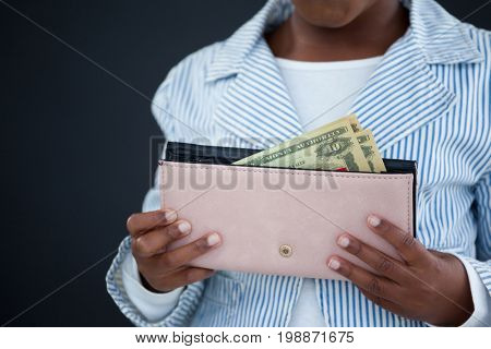 Midsection of businesswoman holding purse with paper currency against wall in office