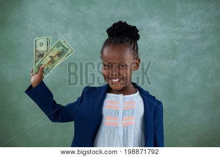 Portrait of smiling businesswoman holding paper currency while standing against blackboard