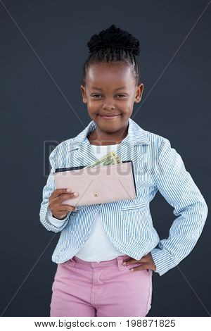 Portrait of smiling businesswoman with hand on hip holding paper currency while standing against gray wall