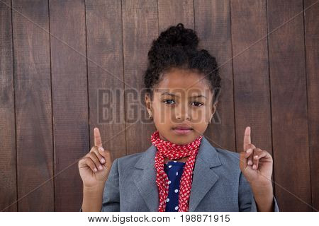Portrait of girl pretending as businesswoman pointing upwards while standing against white background