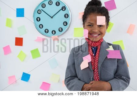 Smiling businesswoman with adhesive notes stuck on suit and head standing against wall
