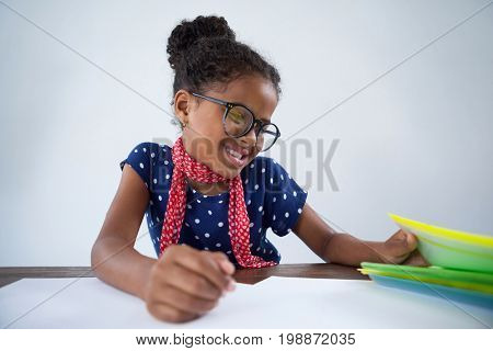 Smiling girl pretending as businesswoman reading documents while sitting at desk against white background