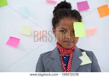 Portrait of businesswoman with sticky notes stuck on head standing against wall