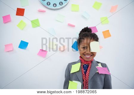 Smiling businesswoman with sticky notes stuck on suit and head standing against wall