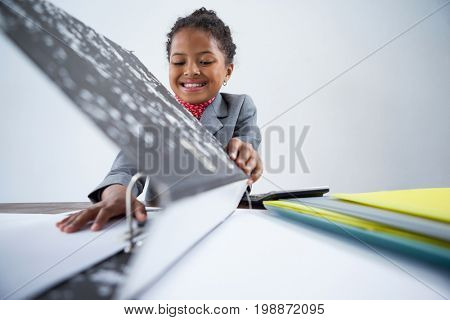 Smiling girl pretending as businesswoman working at desk against white background