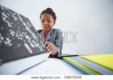 Girl pretending as businesswoman working while sitting at desk against white background