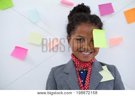 Portrait of smiling businesswoman with sticky notes stuck on head standing against wall