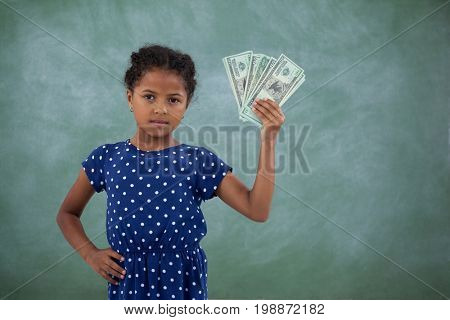 Portrait of girl with hand on hip showing paper currency while standing against wall