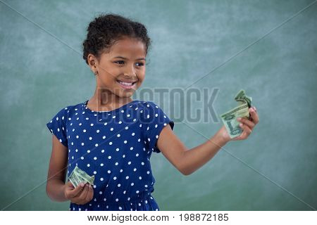 Smiling girl looking at paper currency while standing standing against wall