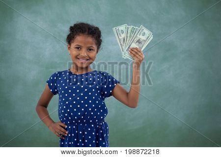 Smiling girl with hand on hip showing paper currency while standing against wall