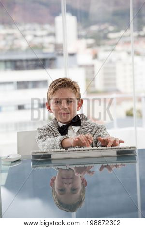 Portrait of businessman using keyboard at conference table in office