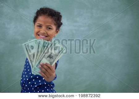 Portrait of happy girl showing paper currency while standing against white background