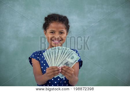 Happy girl showing paper currency while standing against wall