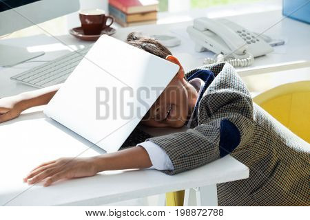 Businessman taking nap on laptop while leaning at desk in office