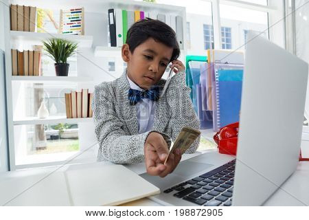 Businessman holding paper currency while talking on smartphone at desk in office