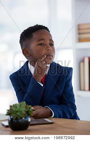 Close up of businessman with hand on chin sitting at desk in office