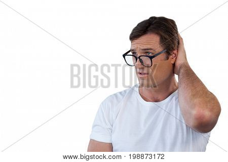 Confused mature man wearing eyeglasses scratching head against white background