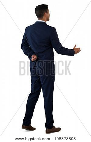 Rear view of businessman with fingers crossed extending arm for handshake  while standing against white background