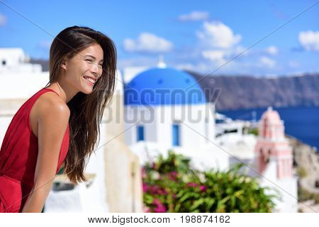 Europe travel cruise destination Santorini woman at Oia tourist landmark attraction, the blue domed church. Happy Asian girl smiling relaxing in summer sun on cruise holiday.