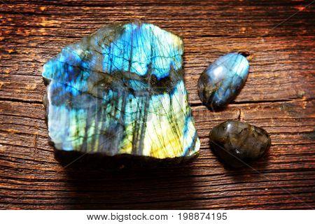 Polished labradorite crystals on wooden board
