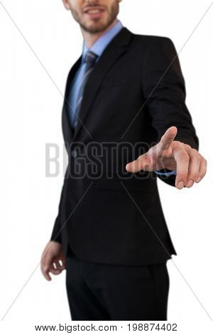 Mid section of businessman in suit touching index finger on invisible interface while standing against white background