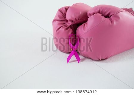 Close-up of pink Breast Cancer Awareness ribbon with boxing gloves pair against white background