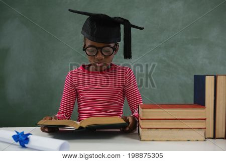 Attentive schoolgirl in mortar board reading book against chalkboard
