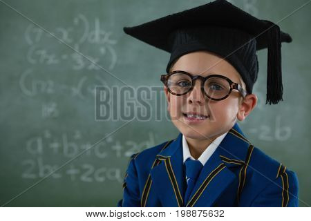 Portrait of schoolboy in mortar board standing against chalkboard