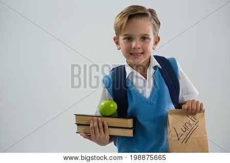 Smiling schoolboy holding books and lunch paper bag against white background