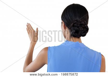 Rear view of businesswoman with hair bun using invisible interface against white background