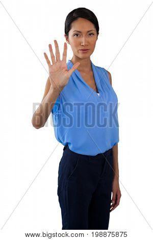 Portrait of businesswoman touching invisible screen while standing against white background