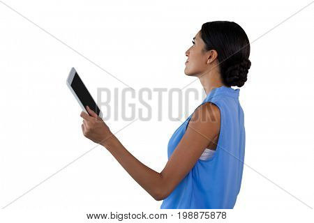 Side view of businesswoman holding tablet while looking away against white background