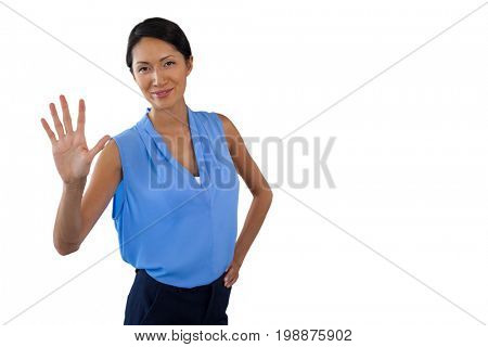 Smiling businesswoman touching interface while standing with hand on hip against white background