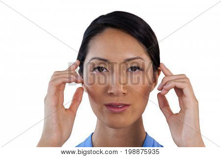 Close up portrait of businesswoman adjusting invisible eyeglasses against white background