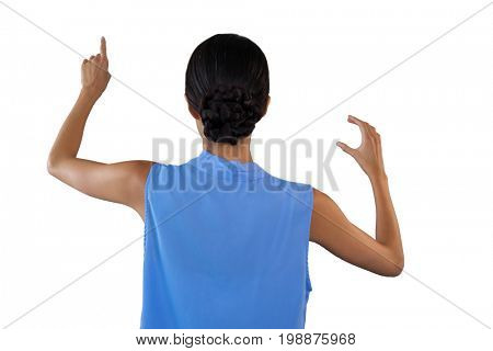 Rear view of businesswoman touching interface while holding something against white background