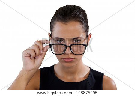Portrait of young businesswoman holding eyeglasses against white background