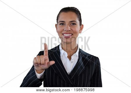 Portrait of smiling businesswoman in suit touching invisible interface against white background