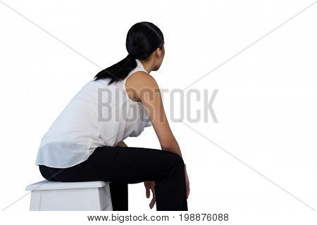 Side view of woman sitting on stool against white background