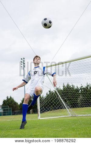 Full length of soccer player playing with ball on field against sky