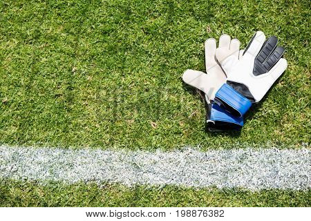 High angle view of sports gloves on playing field