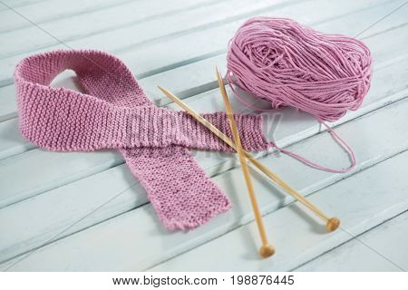 High angle view of pink woolen Breast Cancer Awareness ribbon with crochet needles on white wooden table
