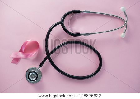 Overhead view of stethoscope by Breast Cancer Awareness ribbon on pink background