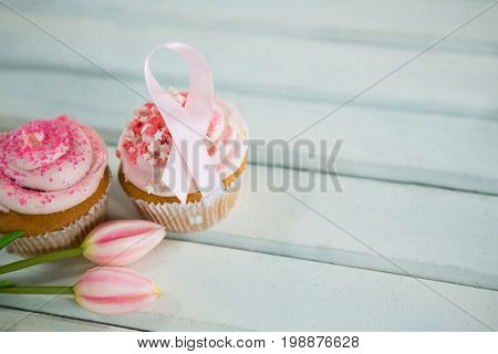 High angle view of Breast Cancer Awareness pink ribbons on cupcakes with tulips over white wooden table
