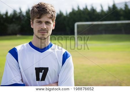 Portrait of Confident male soccer player with arms crossed standing on playing field