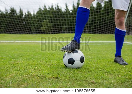 Low section of male soccer player with ball on field against goal post