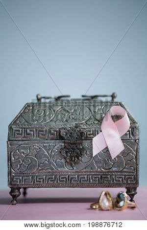 Close-up of pink Breast Cancer Awareness ribbon with rings and chest on table against white background