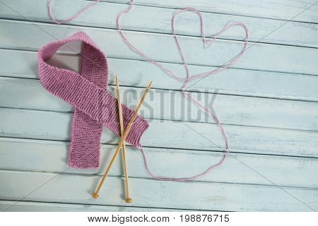 High angle view of pink woolen Breast Cancer Awareness ribbon by crochet needles with heart shape on white wooden table