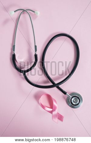 Directly above view of stethoscope by Breast Cancer Awareness ribbon on pink background