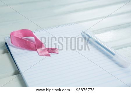 Close-up of pink Breast Cancer Awareness ribbon and spiral notepad with pen on wooden table