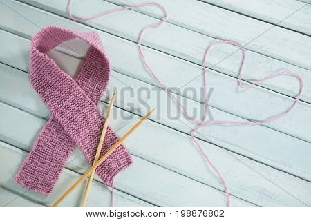 Close-up of pink Breast Cancer Awareness ribbon by crochet needles with heart shape on white wooden table